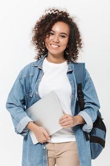 Portret całkiem wesołej, dorywczo afrykańskiej dziewczyny niosącej plecak stojący na białym tle nad białą ścianą, trzymający laptopa