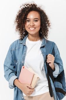 Portret całkiem wesołej, dorywczo afrykańskiej dziewczyny niosącej plecak stojący na białym tle nad białą ścianą, trzymający podręczniki