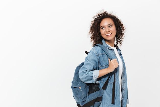 Portret całkiem wesołej dorywczo afrykańskiej dziewczyny niosącej plecak stojący na białym tle nad białą ścianą