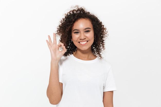 Portret całkiem wesołej dorywczo afrykańskiej dziewczyny stojącej na białym tle nad białą ścianą, pokazując ok gest