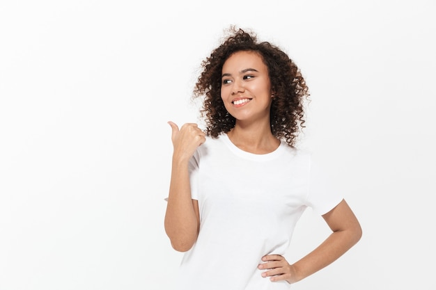 Portret całkiem wesołej, dorywczo afrykańskiej dziewczyny stojącej na białym tle nad białą ścianą, prezentującej miejsce na kopię