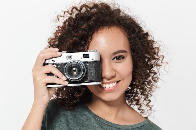 Portret całkiem wesołej dorywczo afrykańskiej dziewczyny stojącej na białym tle nad białą ścianą, trzymającej aparat fotograficzny