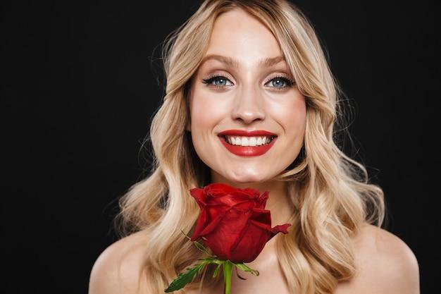 Portret całkiem wesoły młoda blond kobieta z jasny makijaż czerwone usta pozowanie na białym tle gospodarstwa kwiat róży.