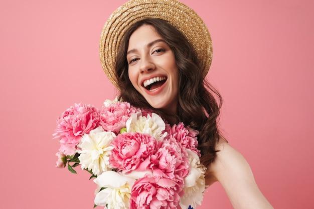 Portret całkiem wesoły śliczna kobieta pozuje na białym tle nad różową ścianą trzymającą kwiaty wziąć selfie przez aparat