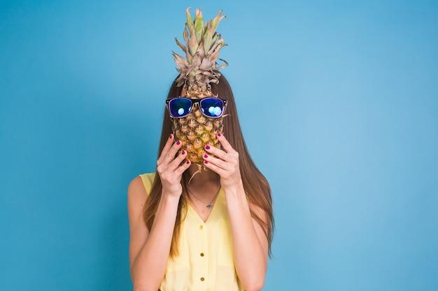 Portret całkiem zabawne lato dziewczyna trzyma ananasa w okularach przeciwsłonecznych na białym tle nad niebieskim tle.