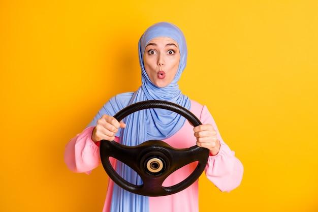 Portret całkiem zabawny funky zdumiony muzułmanka nosząca hidżab trzymając w ręku ster turing na białym tle na żywy żółty kolor