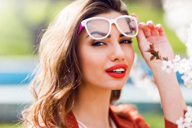 Portret całkiem zmysłowej jasnej kobiety z niesamowitymi czerwonymi ustami, w fajnych okularach