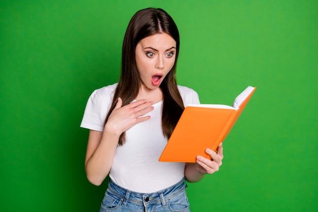 Portret całkiem zszokowanej brunetki młoda dama wygląd książki nosić casual t-shirt na białym tle na zielonym tle
