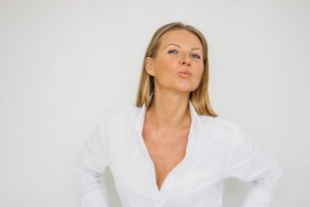 Portret całowanie blondynki czterdzieści rok kobieta z długie włosy w koszula na biel ściany tle odizolowywającym