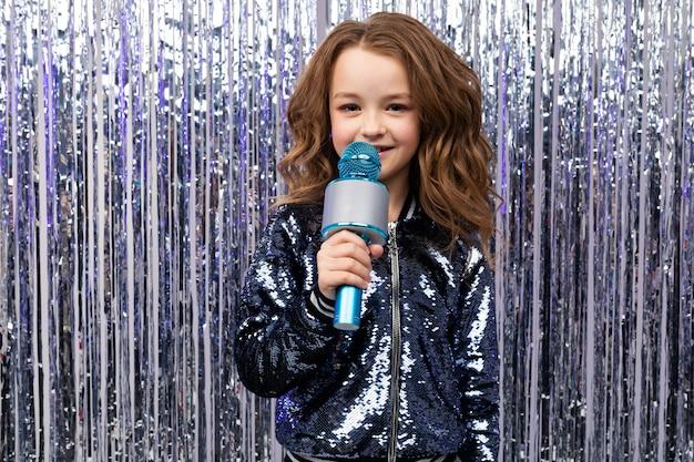 Portret caucasian dziewczyna z mikrofonem na błyszczącej świecidełko ścianie z pustą przestrzenią