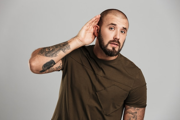 Portret caucasian łysy facet z brodą i wąsem podsłucha z sterczącym ucho, odizolowywający nad szarości ścianą