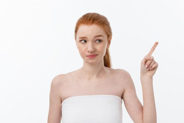 Portret caucasian śliczny w trosce i szoku, wskazujący palec wskazującego na boku, nad białym tłem.