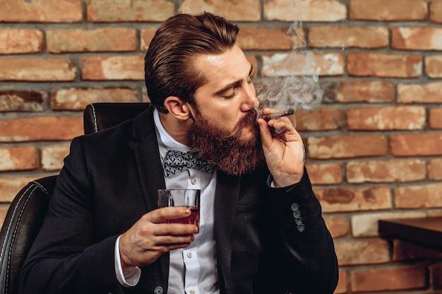 Portret charyzmatycznego atrakcyjnego mężczyzny siedzącego na krześle i trzymającego w ręku szklankę whisky i palącego brązowe cygaro na tle ceglanego muru. koncepcja stylu