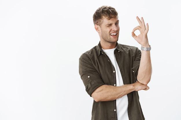 Portret charyzmatycznego chłopaka mrugającego i pokazującym dobry gest, zapewniając, że ma wszystko pod kontrolą i zrozumiał, że stoi intrygująco i sugerując nad szarą ścianą