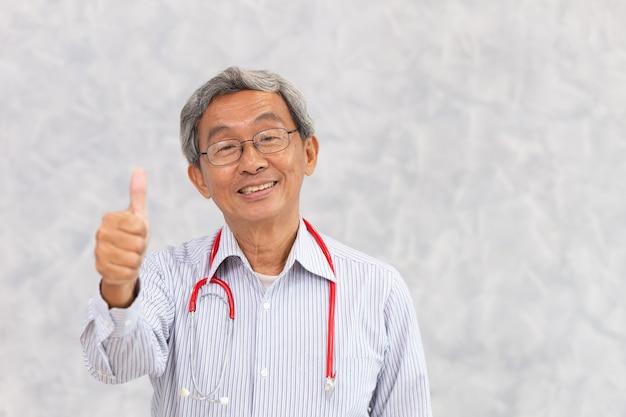 Portret chińskiego lekarza zdrowego starego człowieka azjatyckie starszy stały uśmiech ręki kciuki w górę znak z miejsca na tekst.