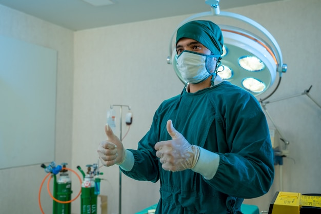 Portret chirurg stojący w sali operacyjnej, gotowy do pracy na pacjencie, pracownik medyczny w mundurze chirurgicznym w sali operacyjnej w szpitalu.