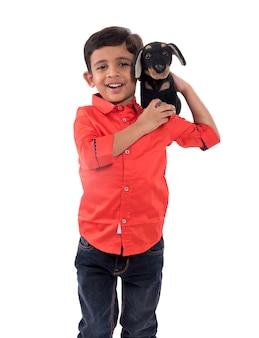 Portret chłopca bawiącego się swoim wypchanym zwierzęciem na białym tle