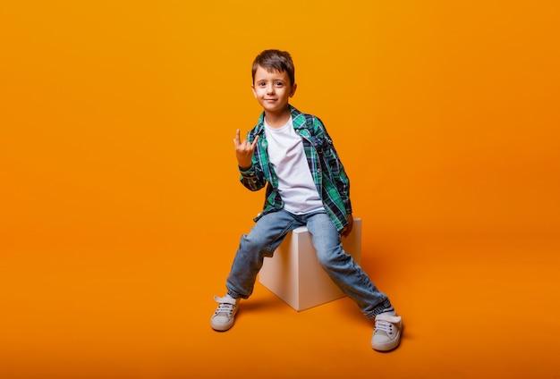 Portret chłopca co rock gest, na białym tle na żółtym tle. przystojny chłopiec kaukaski pokazując rogi gestem w górę.