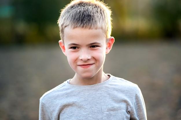 Portret chłopca dziecko na zewnątrz w ciepły słoneczny letni dzień.