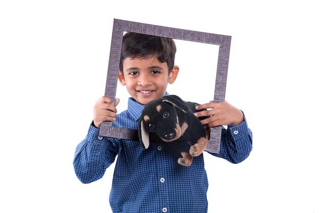 Portret chłopca gospodarstwa zwierzątko wypchane zabawki z ramką na białym tle