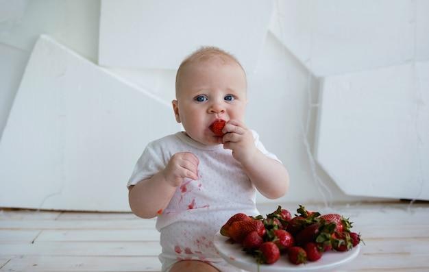 Portret chłopca jedzenie truskawek na białej powierzchni z miejscem na tekst