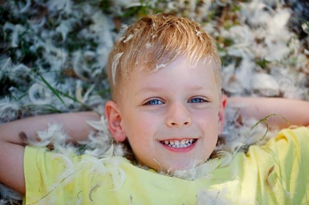 Portret chłopca, który leży na trawie