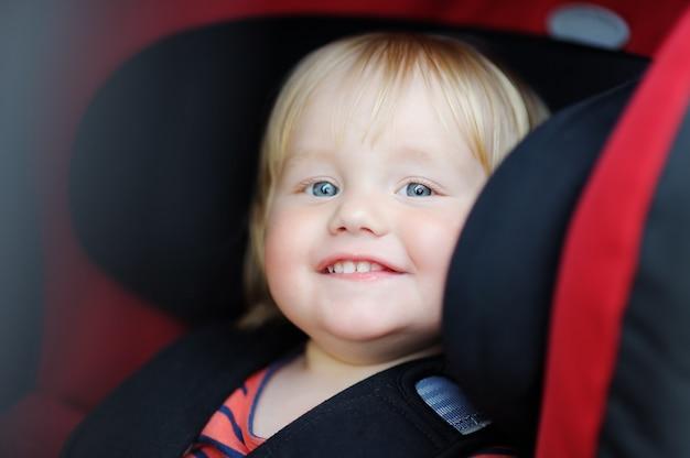 Portret chłopca malucha siedząc w foteliku samochodowym