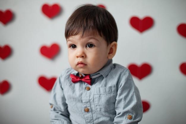 Portret chłopca malucha w koszuli z muszką na tle ściany z sercami na walentynki.