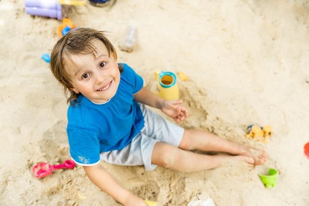 Portret chłopca malucha w wieku przedszkolnym siedzi w piaskownicy i bawi się sam z przyjemnością. edukacyjne gry plenerowe dla dzieci.