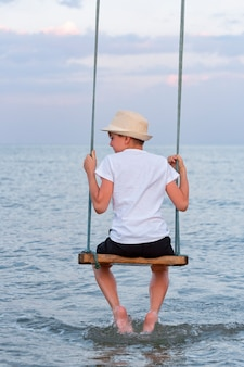 Portret chłopca na huśtawce w wodzie widok z tyłu.