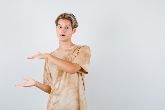 Portret chłopca nastolatka pokazującego znak rozmiaru w koszulce i patrzący pewnie z przodu