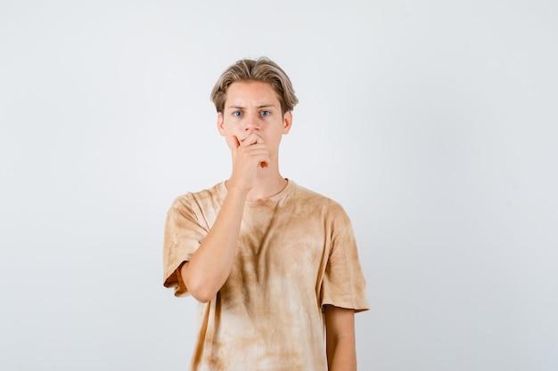 Portret chłopca nastolatka trzymającego rękę na ustach w koszulce i patrzącego na przygnębiony widok z przodu