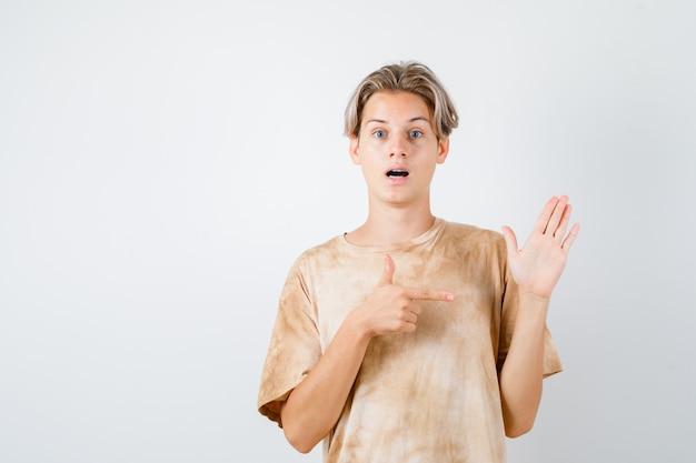 Portret chłopca nastolatka wskazującego na podniesioną rękę w koszulce i patrzącego na zdziwionego widok z przodu