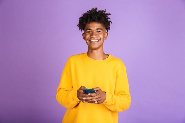 Portret chłopca nastolatka z fryzurą afro, uśmiechającego się i trzymającego smartfona, noszącego słuchawkę bluetooth, odizolowanego na fioletowym tle