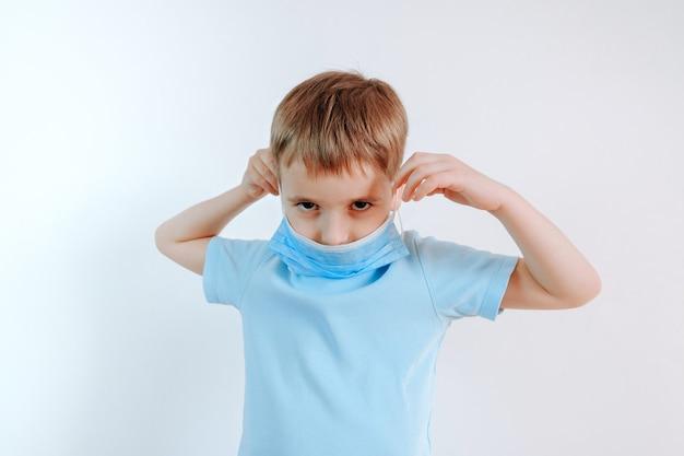 Portret chłopca noszącego ochronną maskę na twarz, aby zapobiec infekcji wirusowej lub zanieczyszczeniu. ochrona przed koronawirusem covid-19