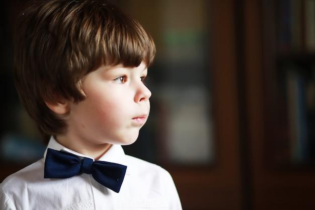 Portret Chłopca O Brązowych Oczach W Koszuli I Czarnej Muszce Na Ciemnym Tle. Dziecko Jest Emocjonalne, Uśmiechnięte, Dobrze Się Bawi, Jest Szczęśliwe. Premium Zdjęcia