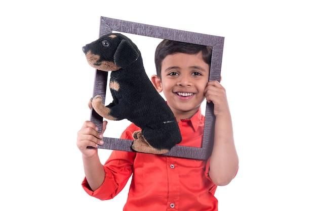 Portret chłopca posiadającego wypchane zwierzę domowe zabawki z ramką na białym
