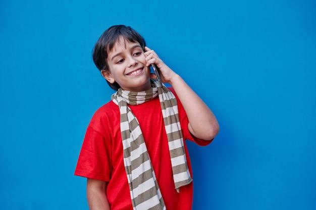 Portret chłopca rozmawia przez telefon komórkowy z czerwoną koszulką i szalikiem