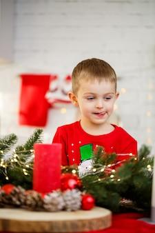 Portret chłopca siedzącego w kuchni przy świątecznym stole, który jest udekorowany na nowy rok. świąteczny wystrój w kuchni