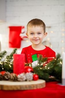 Portret chłopca siedzącego w kuchni przy świątecznym stole, który jest udekorowany na nowy rok