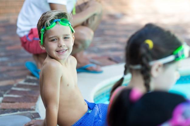 Portret chłopca siedzącego z przyjaciółmi przy basenie