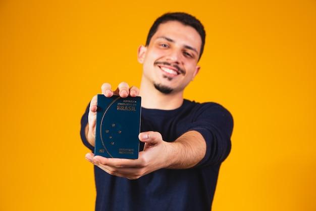 Portret chłopca trzymającego w rękach brazylijski paszport. koncepcja podróży i migracji