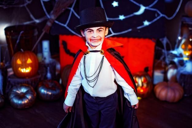 Portret chłopca ubranego w kostium wampira na tle grunge. impreza halloween'owa.