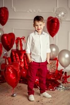 Portret chłopca w białej koszuli i czerwonych spodniach na tle świątecznego wystroju czerwonych kulek w widżecie serc i prezentów. urodziny wakacje lub walentynki