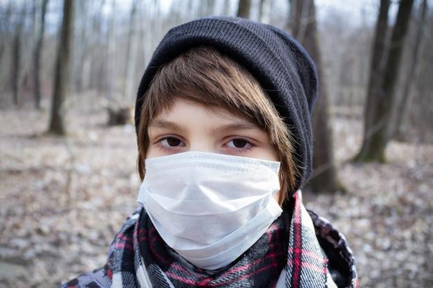 Portret chłopca w jednorazowej masce medycznej, szaliku i kapeluszu na tle drzew. koronawirus pandemia.