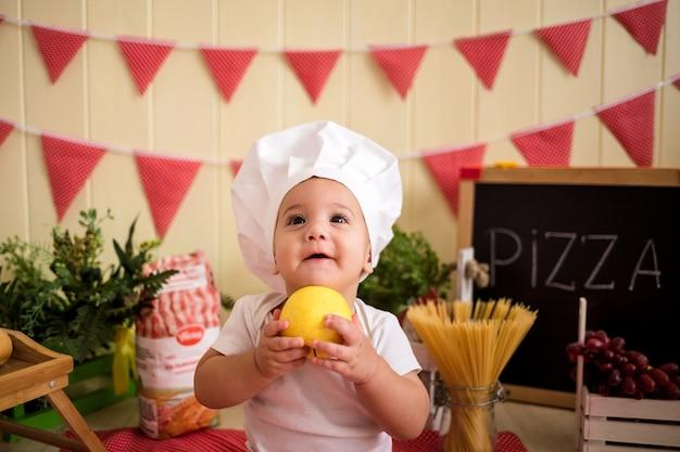 Portret chłopca w kapeluszu szefa kuchni z jabłkiem w ręku