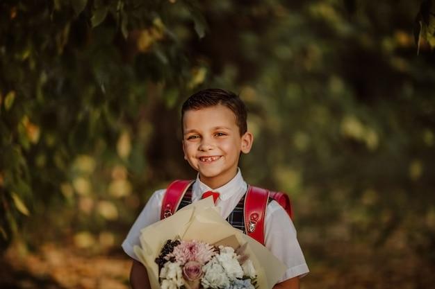 Portret chłopca w mundurek szkolny, trzymając bukiet kwiatów w parku