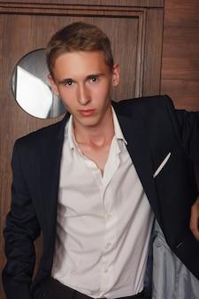 Portret chłopca w szkole. ubrany formalnie w czarny garnitur, krawat, białą koszulę, ręce w kieszeniach, młody przystojny student stojący przed drzwiami biura w stylu vintage na kampusie, patrząc na ciebie.