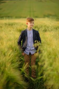 Portret chłopca w zielonym polu pszenicy.