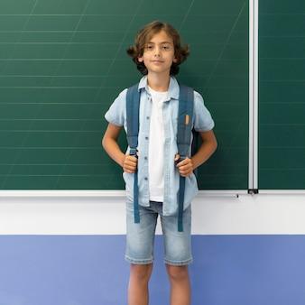 Portret chłopca z plecakiem w klasie